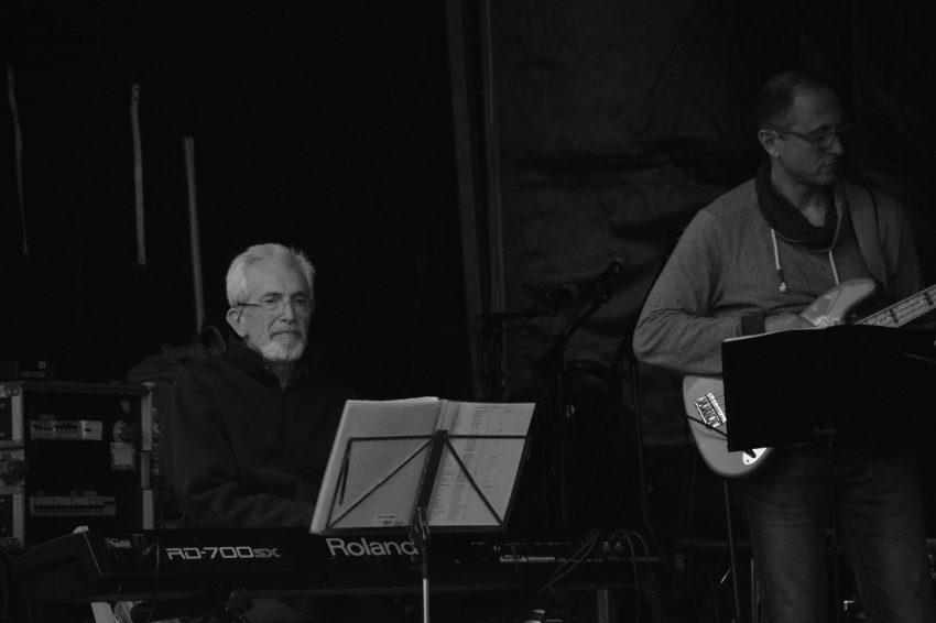 Imagem em preto e branco mostrando um idoso no centro tocando teclado com uma estante para partitura na frente. Ao seu lado direito há um baixista que também está com uma estante para partitura à sua frente.