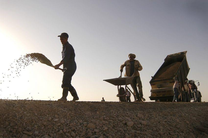 Homens trabalhando espalhando terra, um joga terra com a pá, outro leva a terra com um carrinho de mão.