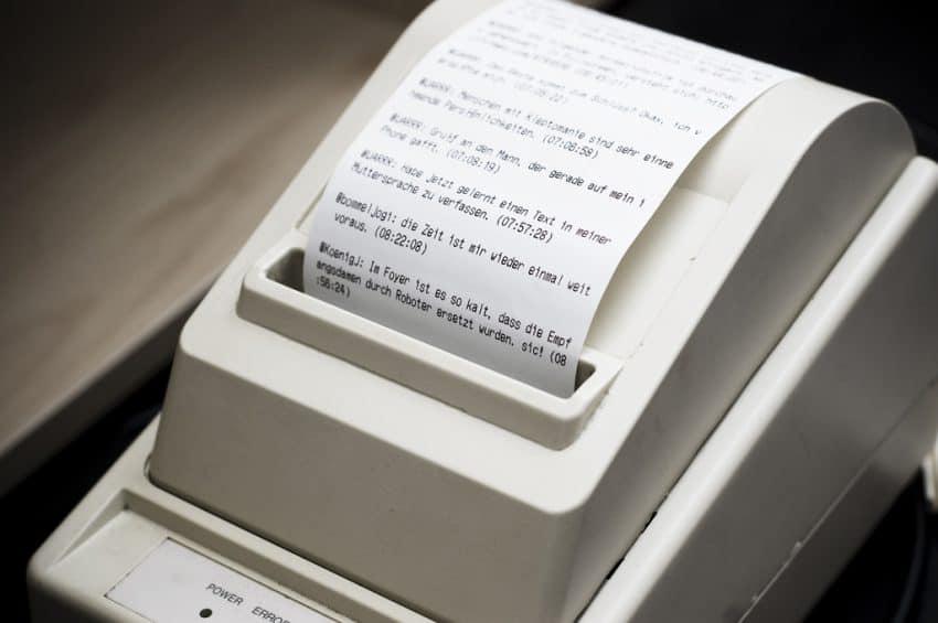 Imagem mostra uma impressora térmica fazendo uma impressão.