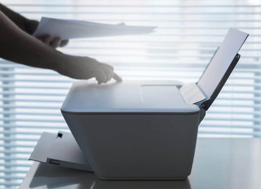 Pessoa usando uma impressora multifuncional branca.