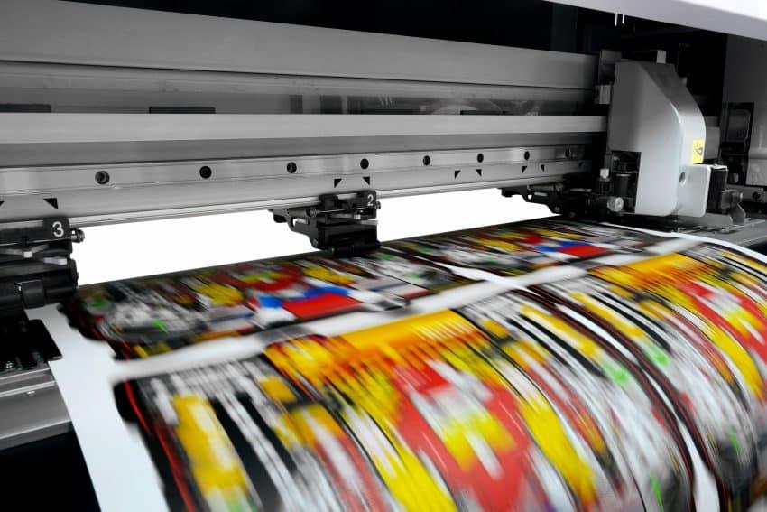 Imagem mostra uma impressora fazendo a impressão de imagens em um papel fotográfico.