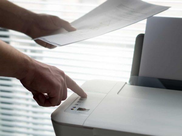Pessoa utilizando impressora multifuncional branca com papéis na mão.