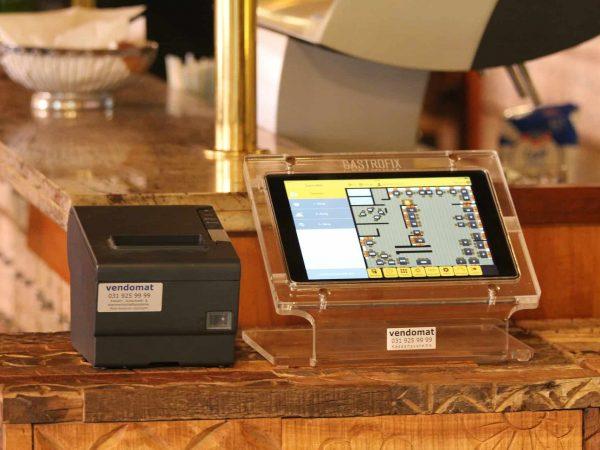 Imagem mostra uma impressora térmica ao lado de um tablet, que está acoplado a uma estrutura de plástico, e ambos estão em cima de um móvel de madeira.