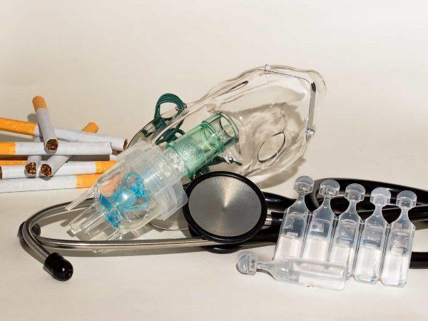 Foto de uma máscara de inalação, junto de um estetoscópio e alguns tubinhos transparentes. Ao fundo, alguns cigarros.