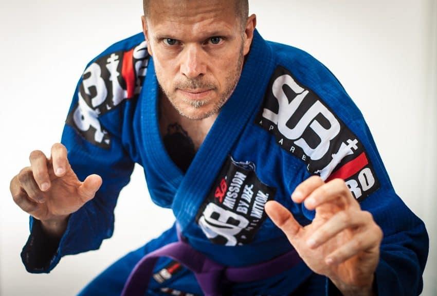 Imagem mostra um homem vestido com kimono e faixa em posição de luta de jiu-jitsu.