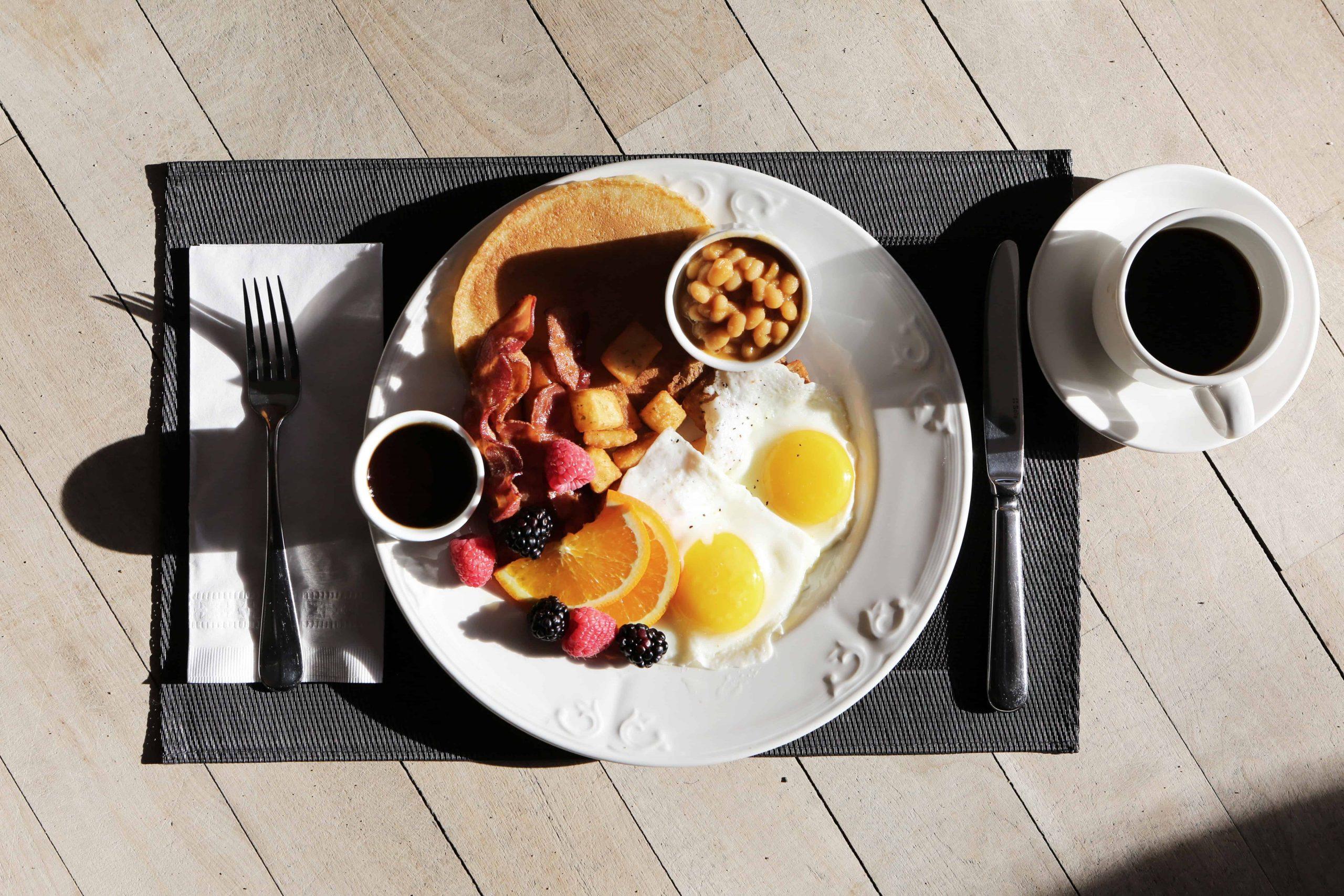 Na foto está um prato com comida de café da manhã em cima de um jogo americano na cor preta com uma xícara de café ao lado.