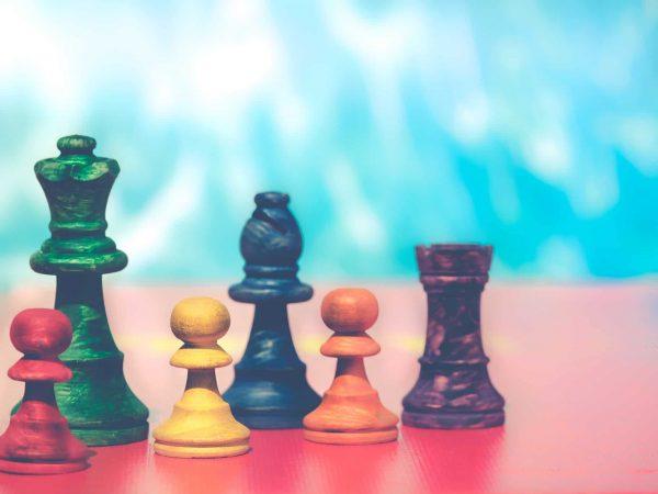 Mesa vermelha com 6 pinos de xadrez coloridos