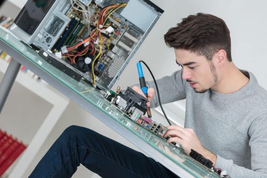 Jovem sentando em uma bancada usando uma estação de solda em componentes de um computador que está ao lado.