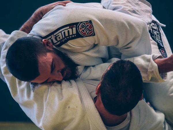 Foto de dois homens de kimono branco lutando jiu jitsu.