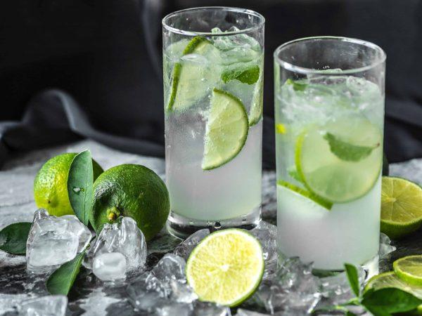 Foto de dois drinks de limão em cima de uma mesa, com limões e pedras de gelo em volta.