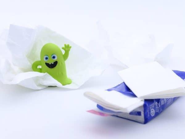 Imagem de pacote de lenços umedecidos com bonequinho verde simbolizando um vírus.