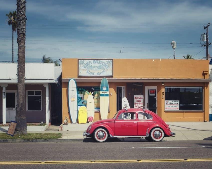 Imagem mostra um carro vermelho estacionado e no plano de fundo, a fachada de uma loja de surf com várias pranchas de surf encostadas na parede.