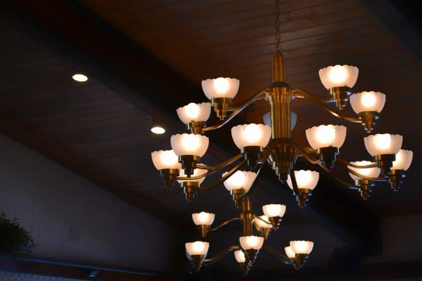 Imagem de lustre em estilo tradicional fixado em teto de madeira.
