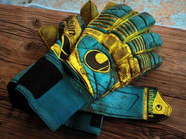 Imagem de luvas de goleiros azuis e amarelas, desgastadas e sobre bancada de madeira