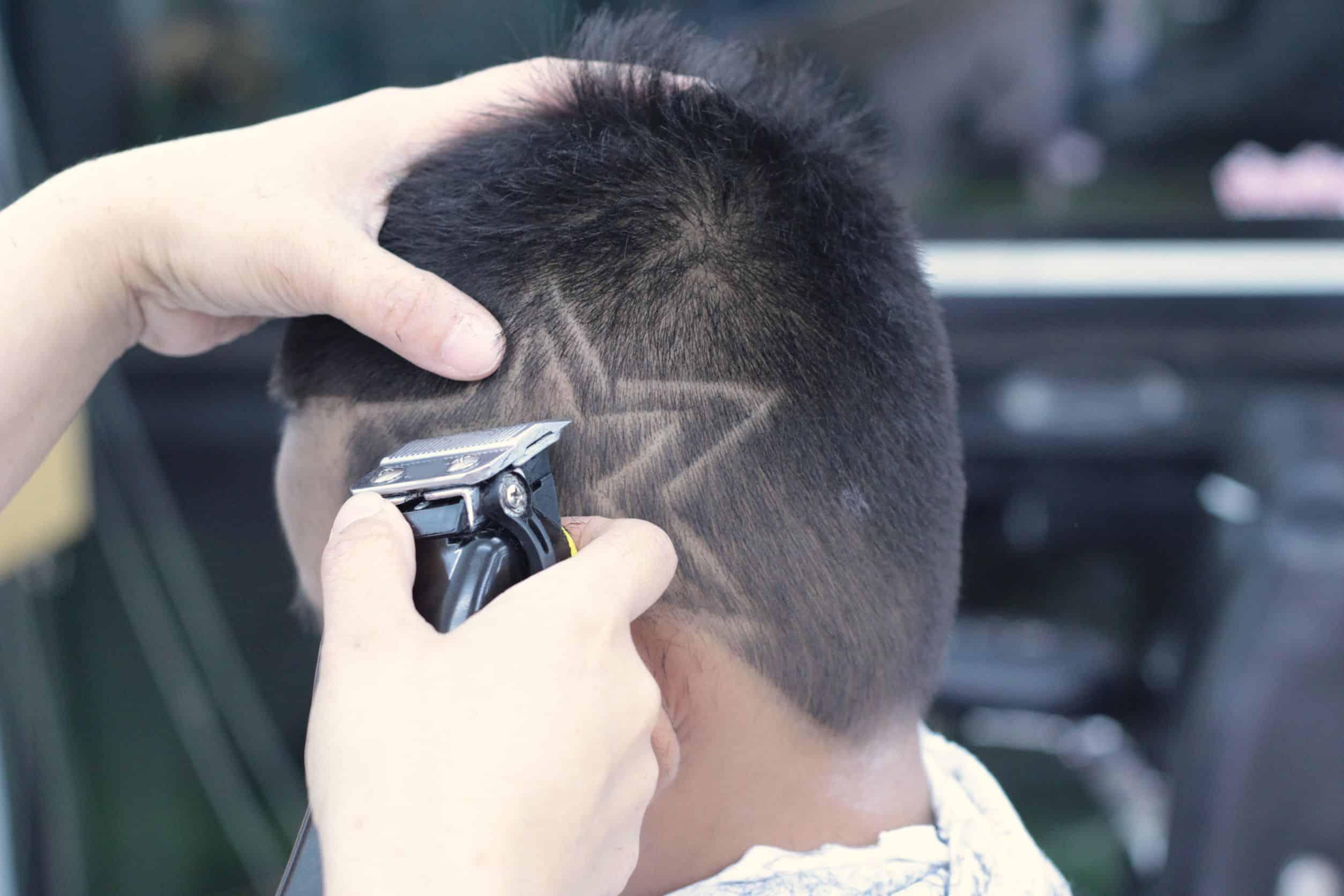 Mão segurando máquina de cortar cabelo e fazendo um desenho de estrela na cabeça do cliente.