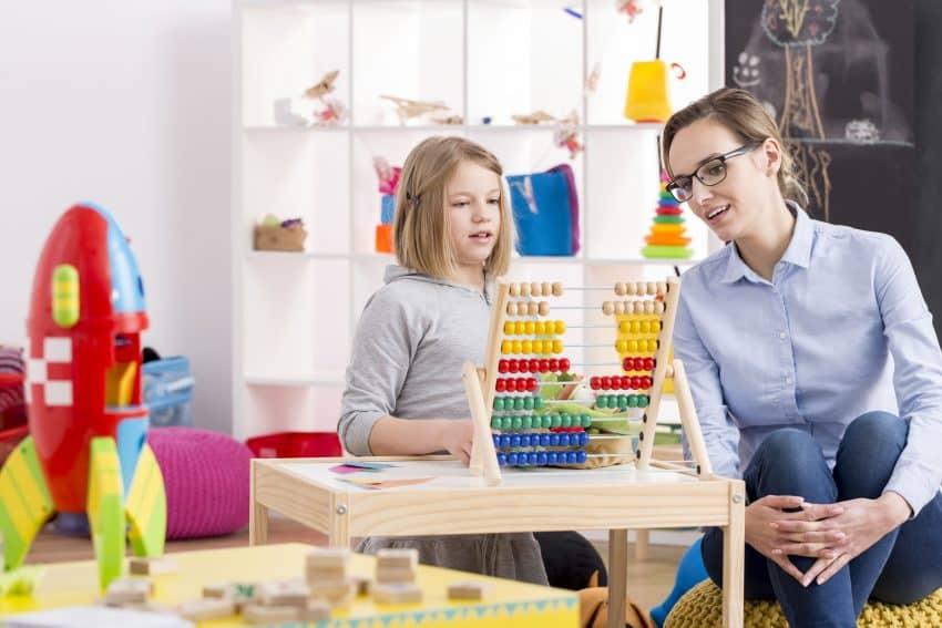 Mãe e filha usando ábaco em uma sala de brinquedos.