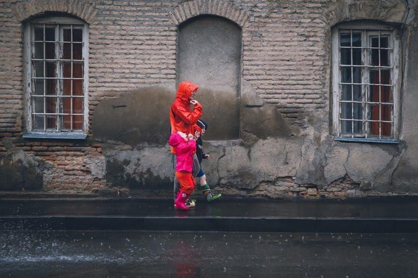 Imagem de pessoa andando na rua com duas crianças usando capas de chuva coloridas.