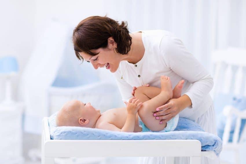 Mamãe conversando com bebê que está de fralda no trocador.