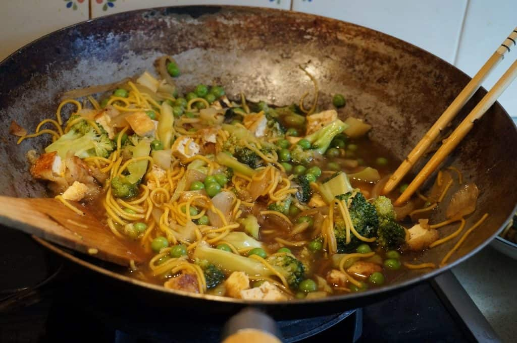 Panela wok com Yakisoba de legumes sendo cozinhado e mexido com colher de pau.