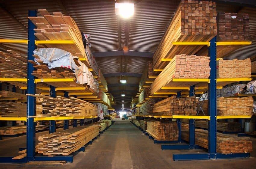 Galpão onde estão mostradas prateleiras com madeiras de diversos tamanhos, a maioria de grande espessura.