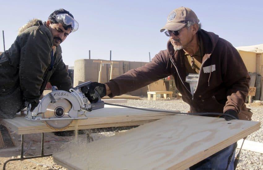 Carpinteiro realizando corte em madeira utilizando uma serra circular. Um segundo carpinteiro auxilia a segurar a peça a ser cortada.