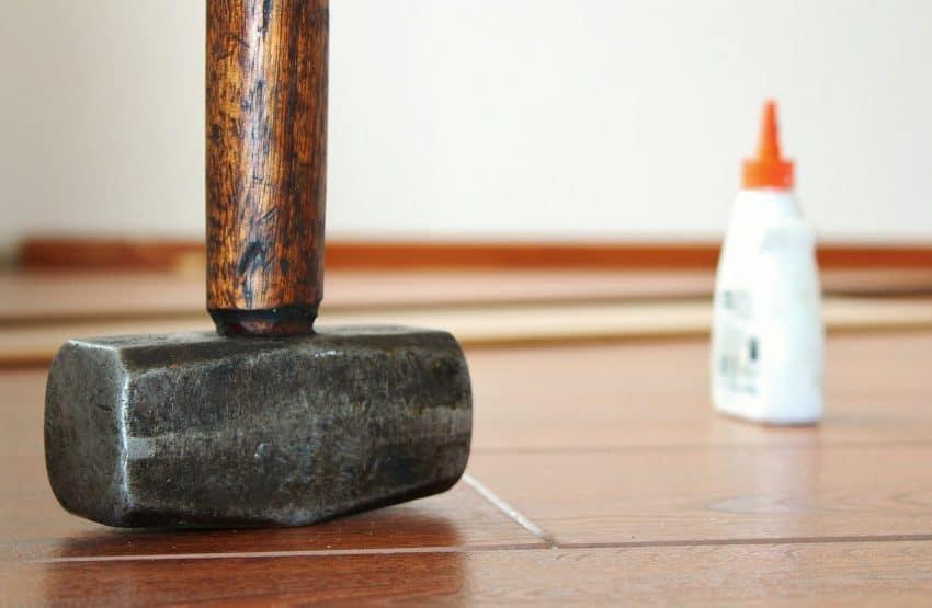 Imagem mostra um martelo com partes em madeira e metal ao lado de um tubo de cola.
