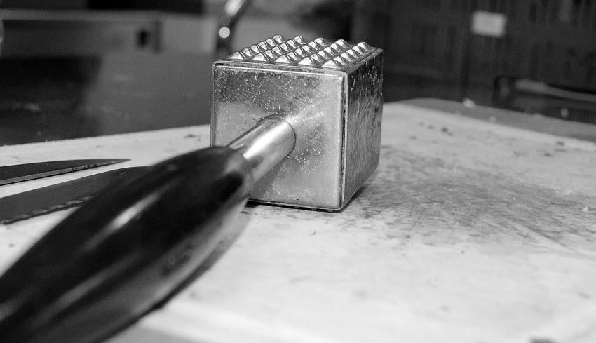 Imagem de um amaciador de carne do tipo martelo com cabo de plástico.
