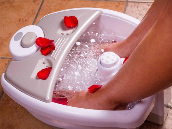 Na foto os pés de uma mulher dentro de um massageador elétrico.