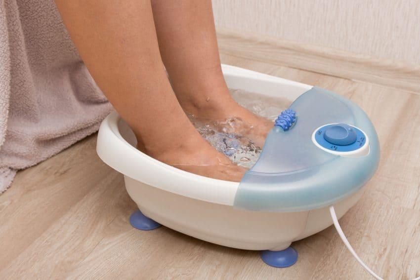 Pés de uma mulher dentro de um massageador de pés.