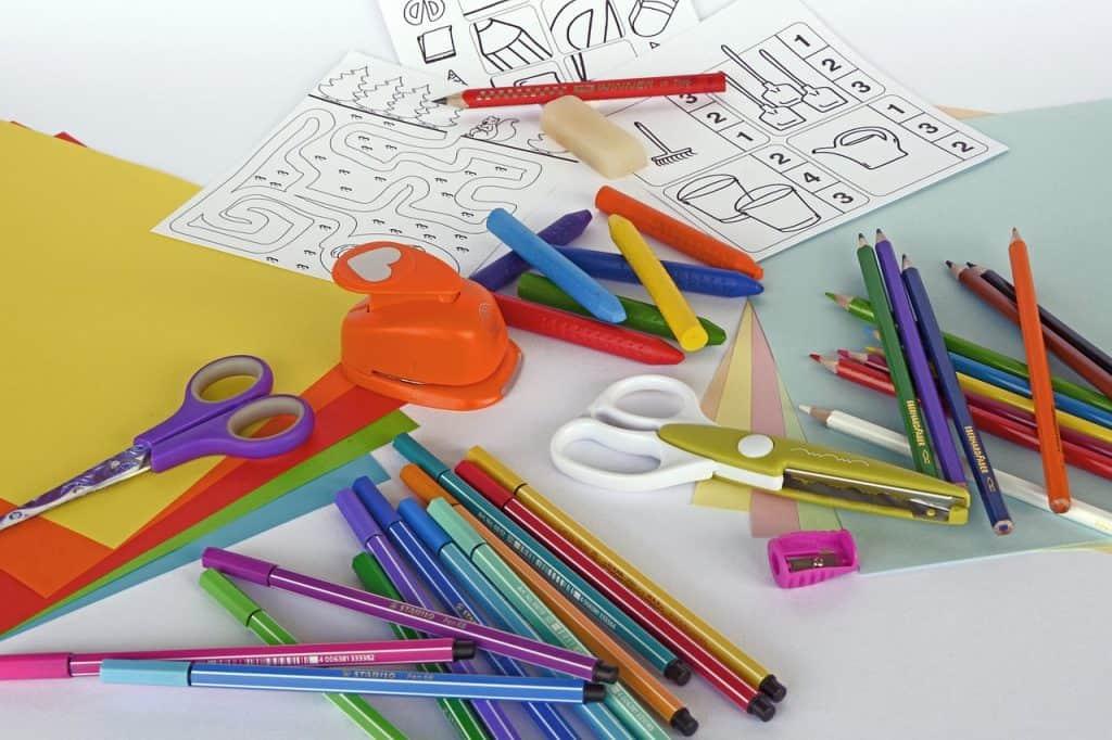 Imagem mostra mesa cheia de itens escolares bagunçados.