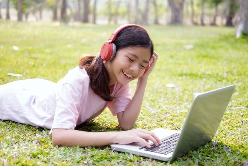 Imagem de uma menina deitada no gramado, enquanto mexe no computador e usa um fone de ouvido sem fio.