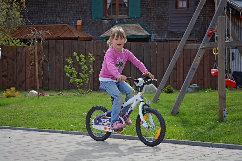 Menina pedalando bicicleta branca.