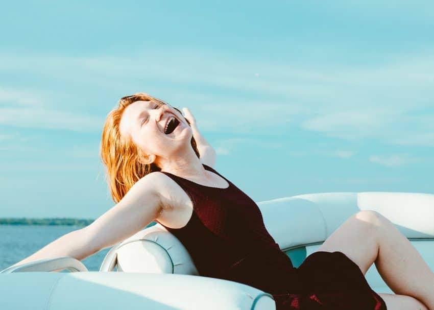 Imagem de uma menina ruiva tomando sol em um barco.