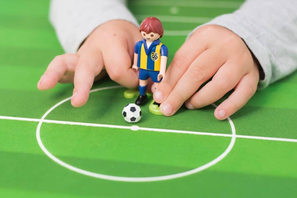Imagem de um menino brincando com um bonequinho de Playmobil.