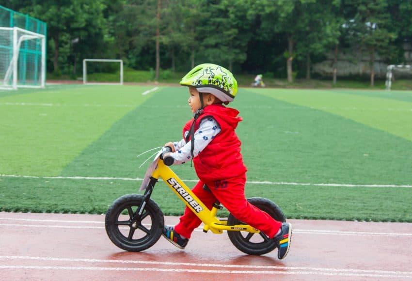 Imagem de menino com capacete andando com uma bicicleta amarela.