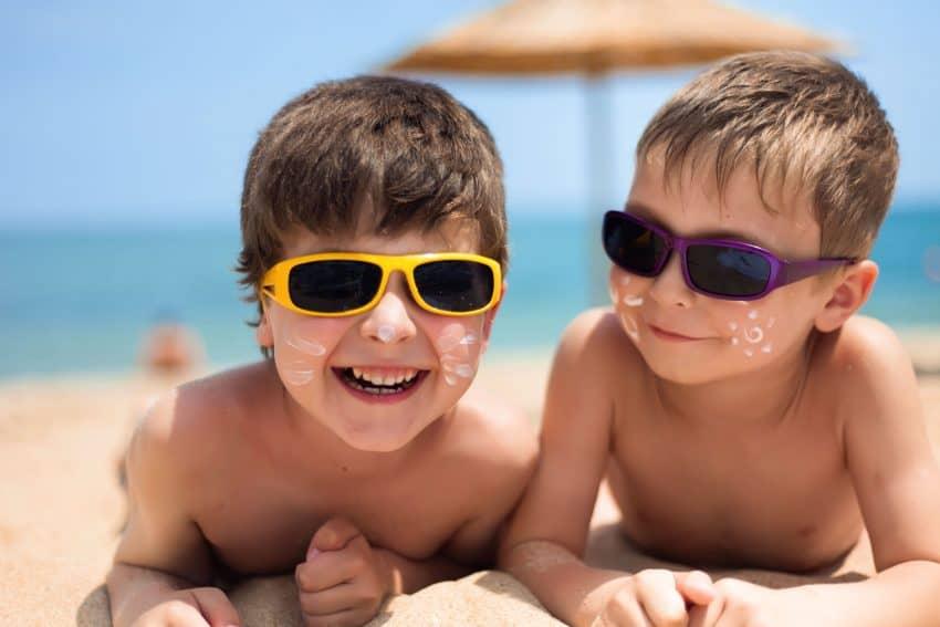 Imagem de dois meninos sorrindo na praia com protetor no rosto.