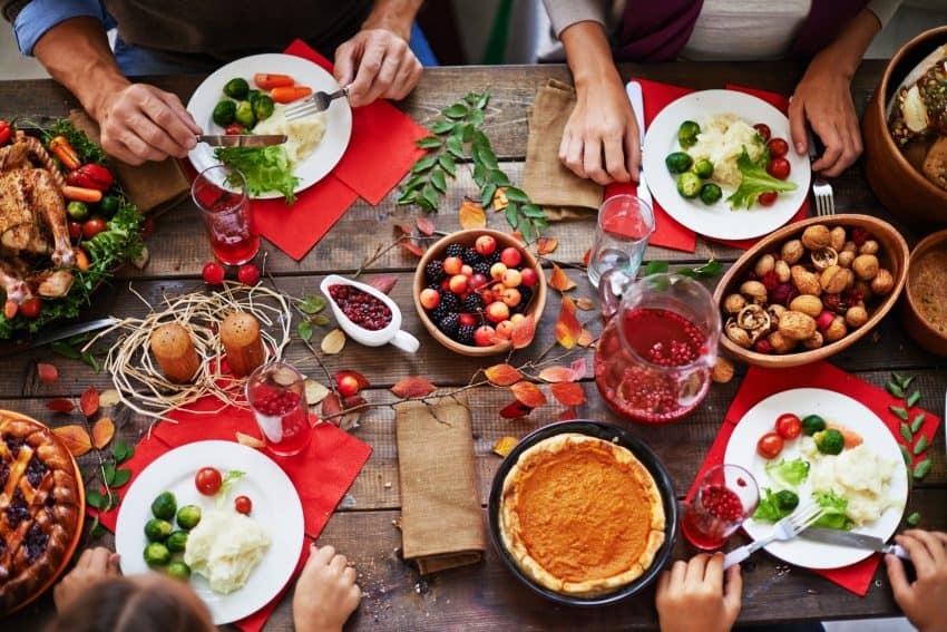 Grupo de pessoas sentado a mesa, mesa bem completa e decorada.