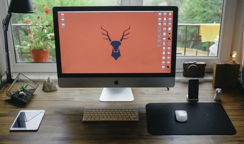 Imagem de uma mesa trabalho com monitor grande de frente para uma janela com vista para um jardim.