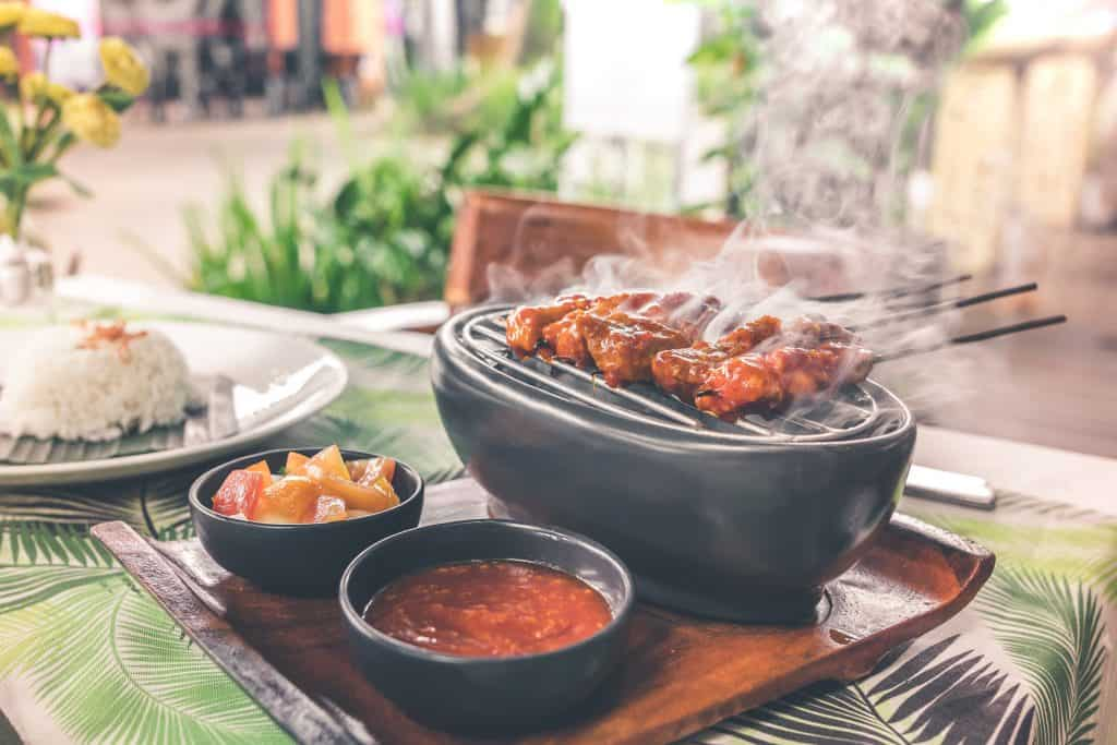 Na foto está uma mesa posta com um prato com arroz e uma bandeja contendo um caldo, frutas cortadas e uma grelha com espetos.