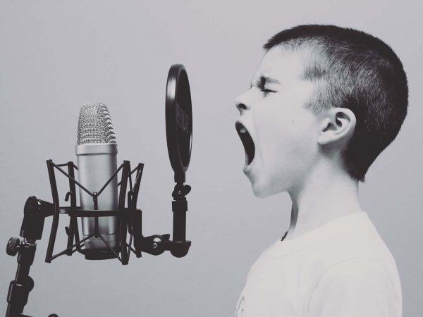 Menino em frente a um microfone gritando.