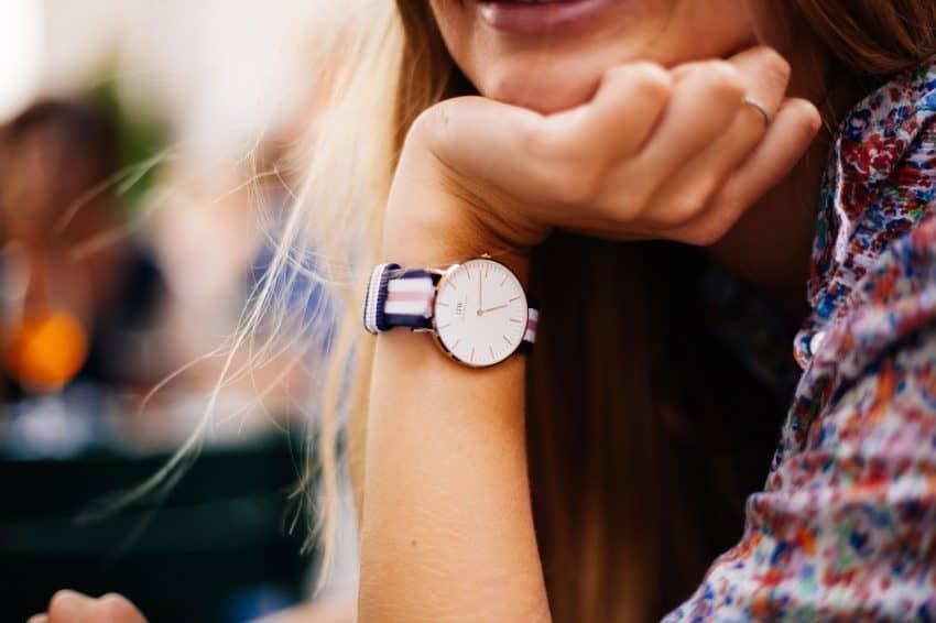 Imagem de relógio em destaque no pulso de uma mulher.