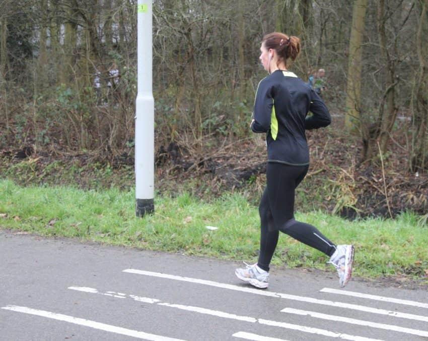 Imagem mostra uma mulher correndo na rua com um fone de ouvido de corrida.
