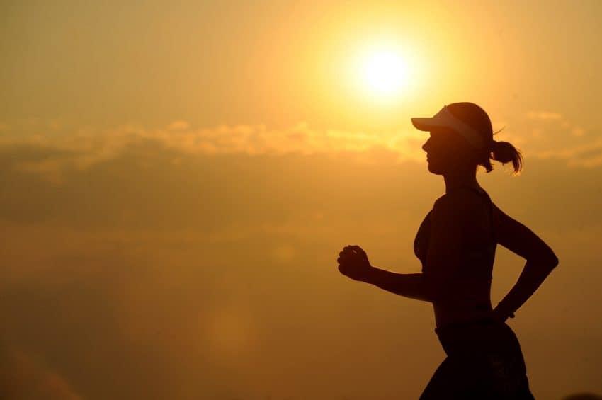 A imagem mostra a silhueta de uma mulher correndo com a luz do sol ao fundo.