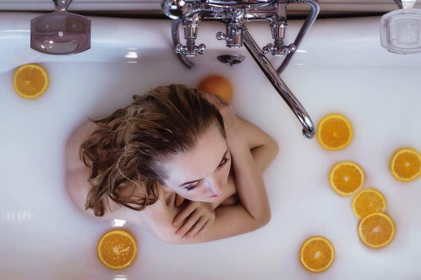 Uma mulher em uma banheira rodeada por fatias de laranja.