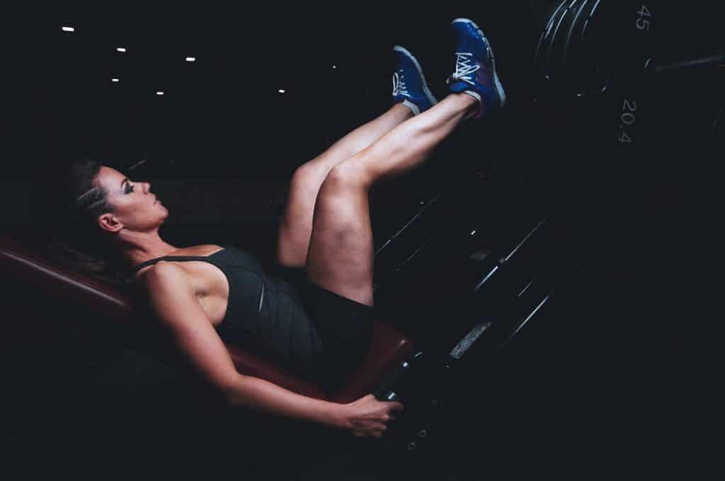 Mulher com roupas de academia e tênis fazendo leg press em um local escuro.