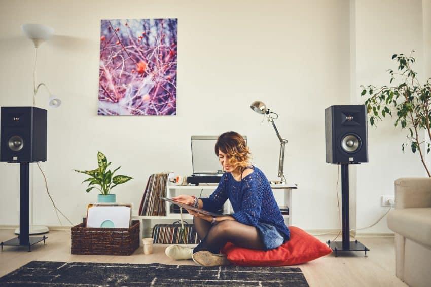 Menina sentada em uma almofada no chão da sala mexendo em discos de vinil.