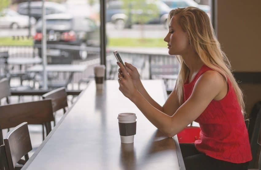 Mulher sentada na bancada de uma cafeteria mexendo no celular.