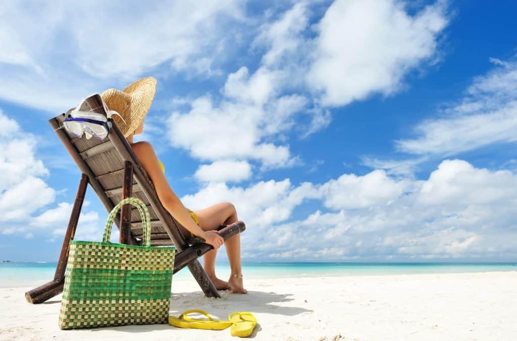 Foto mostra uma mulher sentada em cadeira de praia com a bolsa e chinelo na areia. Ao fundo, o mar e o céu azul.