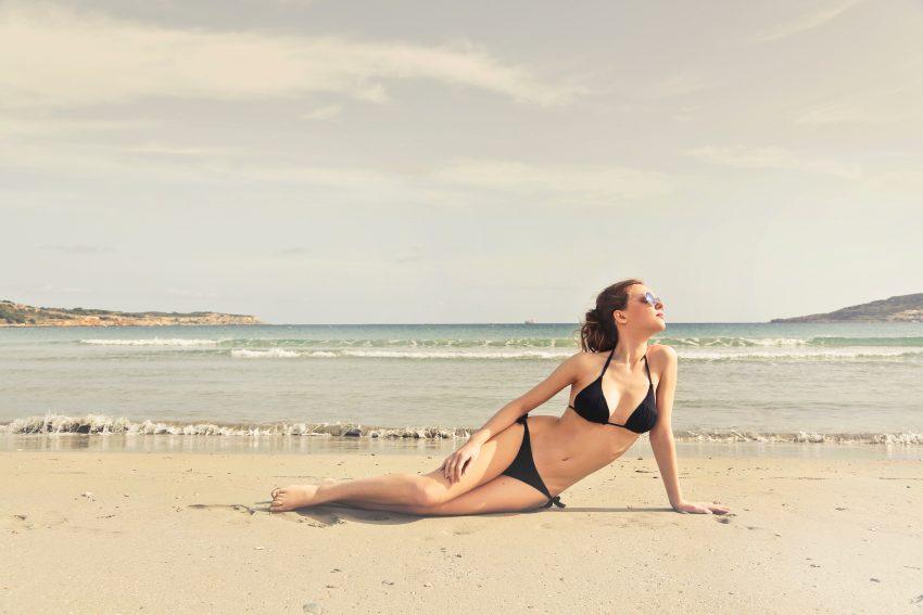 Foto de uma mulher de biquíni preto, sentada na areia de uma praia, olhando para longe, com o mar ao fundo.