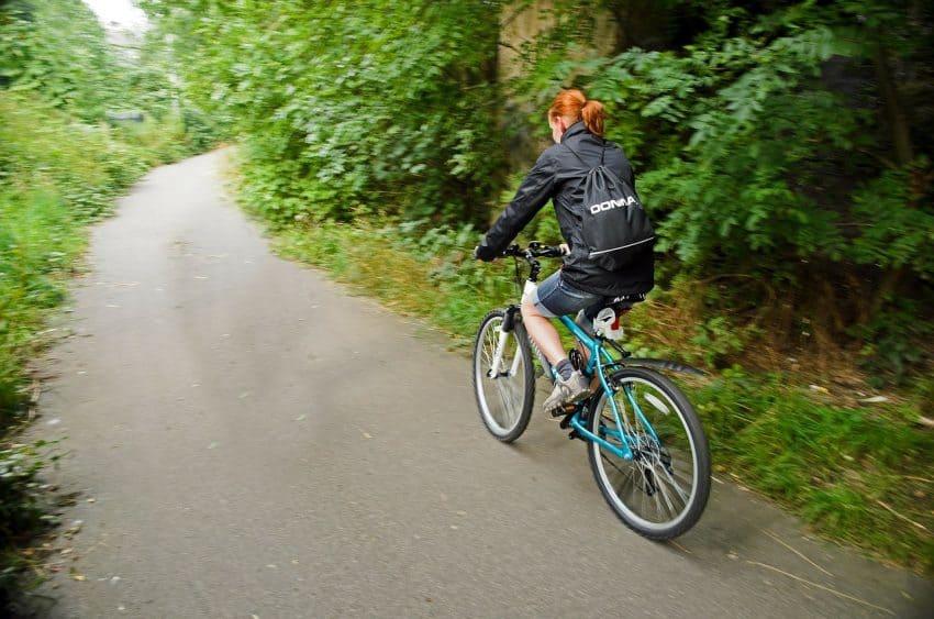 Mulher pedalando no parque.
